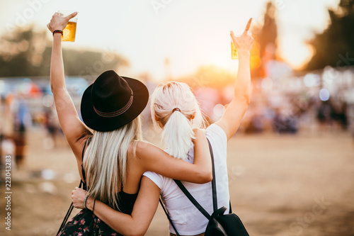 Cadres-photo bureau Magasin de musique Two female friends drinking beer and having fun at music festival.Back view