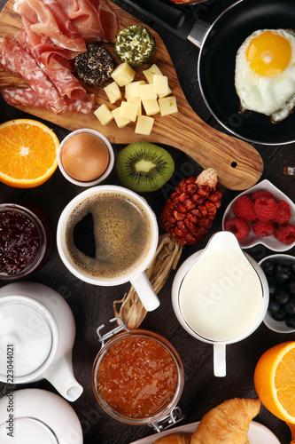 Fototapeta breakfast on table with bread buns, croissants, coffe and juice. obraz