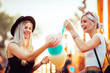 canvas print picture Shot of happy female friends in amusement park eating cotton candy. Two young women enjoying a day at amusement park.