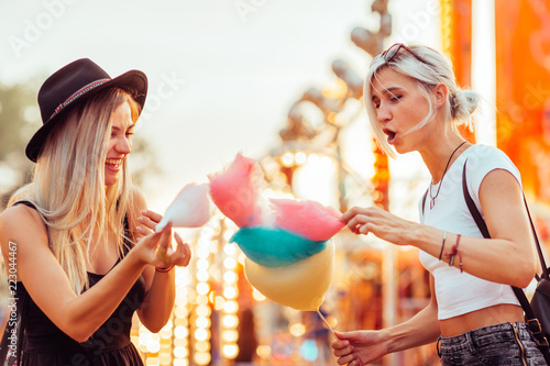 Poster Attraction parc Shot of happy female friends in amusement park eating cotton candy. Two young women enjoying a day at amusement park.