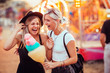 canvas print picture - Shot of happy female friends in amusement park eating cotton candy. Two young women enjoying a day at amusement park.