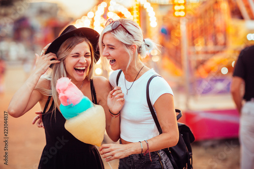 Poster Amusementspark Shot of happy female friends in amusement park eating cotton candy. Two young women enjoying a day at amusement park.