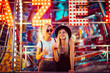 canvas print picture Happy female friends in amusement park drinking beer. Two young women enjoying night at amusement park.