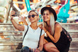 canvas print picture Happy female friends in amusement park taking selfie. Two young women enjoying night at amusement park.