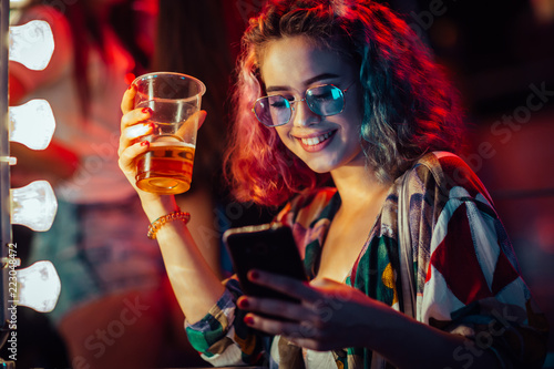 Fototapeta Young woman at the festival drinking beer and using mobile phone