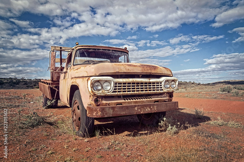 Foto op Aluminium Oceanië Australia – Outback desert with an old vintage abandoned car near the track under cloudy sky