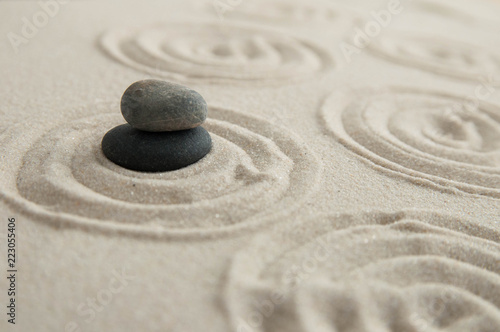 Photo Stands Stones in Sand Pyramids of gray zen stones on the sand with wave drawings. Concept of harmony, balance and meditation, spa, massage, relax