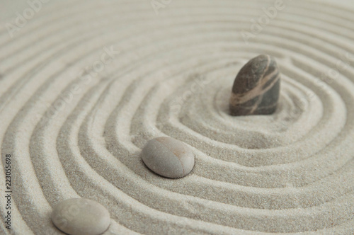 In de dag Stenen in het Zand Pyramids of gray zen stones on the sand with wave drawings. Concept of harmony, balance and meditation, spa, massage, relax