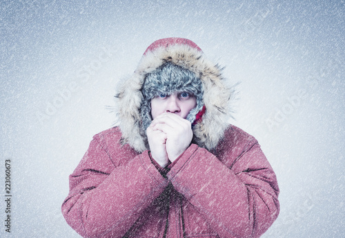 Frozen man in red winter clothes warming hands, cold, snow, frost, blizzard
