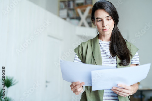 Portrait of brunette young woman holding two documents and reading them, copy space