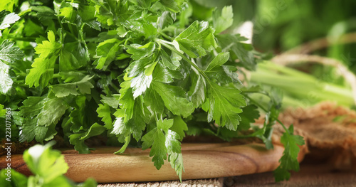 Fresh green parsley in bunch, old wooden table, selective focus