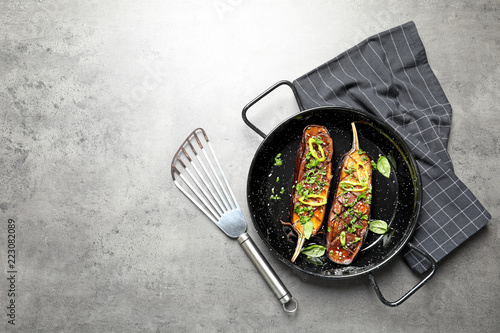 Frying pan with fried eggplant slices on table, top view. Space for text