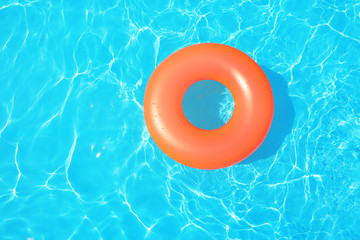 Inflatable ring floating in swimming pool on sunny day, top view