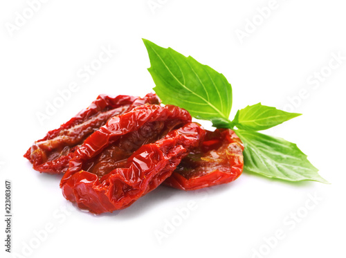 Fotografía  Tasty sun dried tomatoes with green leaves on white background
