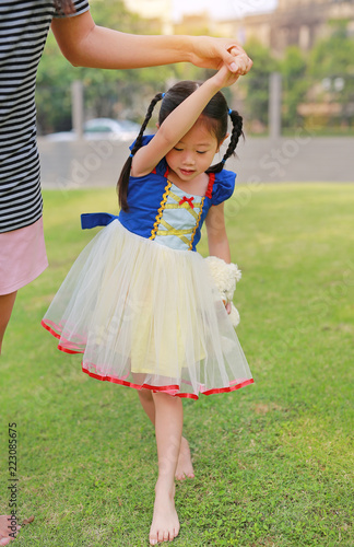 Fotografia, Obraz  Cute Asian child girl dressed a fantasy outfit holding teddy bear and unshod walking on green grass garden with mother hand in hand