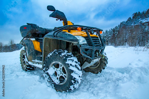 ATV is a yellow color. ATV rentals. Quad bike on the background of the mountain. SUV. Traveling in winter on an off-road car. Quad bike against the snow.