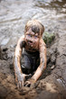 Dirty Little Boy Child Playing in Mud while Swimming in the River on a Summer Day