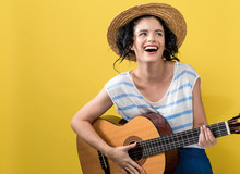 Young Woman With A Guitar On A Yellow Background