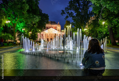 Foto op Canvas Theater Young girl enjoying the cityscape at night - fountains in front the National Theatre building in Sofia, Bulgaria