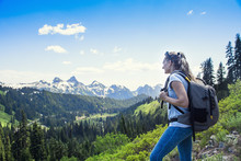 A Woman Hiking Near A Beautiful Scenic Mountain Range At Mount Rainier National Park In Washington USA. Looking Up At The Snow Capped Glaciers During A Day Hike