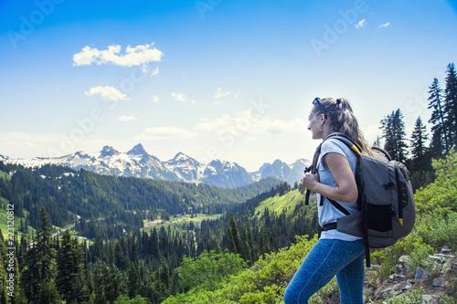 Valokuva  A woman hiking near a beautiful scenic mountain range at Mount Rainier National Park in Washington USA