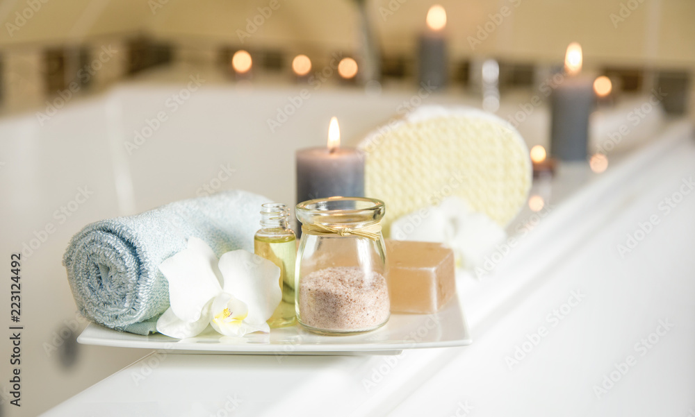 Fototapeta White ceramic tray with home spa supplies in home bathroom for relaxing rituals. Candlelight, salt soap bar, bath salt in jar, massage, bath oil in bottle, blue rolled towel, natural sponge.