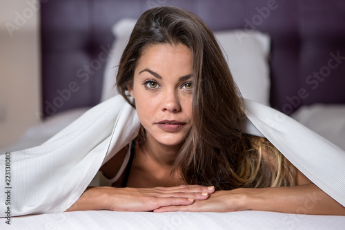 Beautiful young brunette lying in bed