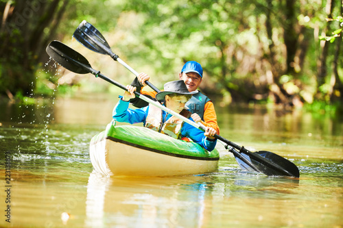 Kayaking on river in forest Wallpaper Mural