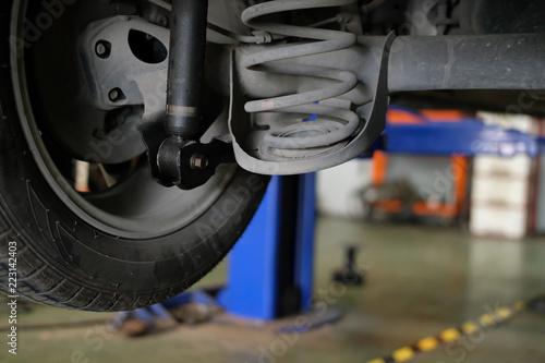 Photo damaged rear car shock absorber & spring in auto repair garage