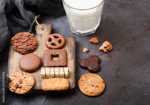 Tuinposter Koekjes Oat and chocolate cookies selection with glass of milk on wooden board on stone kitchen table background.