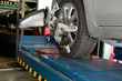 car tyre clamped with aligner reflector adjustment tool for wheel alignment check in auto garage service