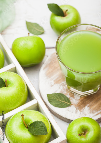 Poster Légumes frais Glass of fresh organic apple juice with granny smith green apples in box on wooden background