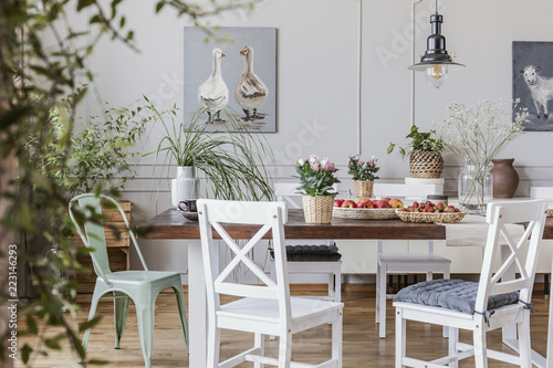 Fotografia, Obraz Flowers on wooden table in white cottage dining room interior with posters and chairs