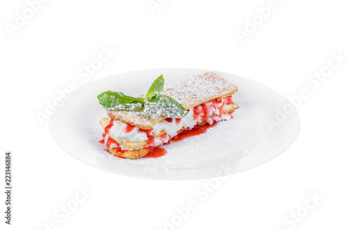 Foto op Plexiglas Klaar gerecht Dessert with cream, whipped cream, berry, strawberry syrup and biscuits, puff pastry, mint leaf, powdered sugar, on a plate, isolated white, side view. For the menu of a cafe, restaurant, bar