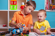 Two boys ?hild collects robot from the plastics details