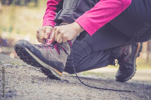 фотографія  Junge Frau bindet ihre Wanderschuhe, Wanderung