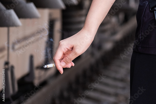 Fotografia  In the photo, a woman's hand holds a lit cigarette.