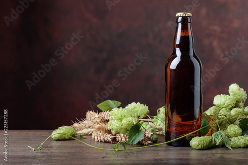 Foto op Aluminium Bier / Cider Bottle of beer, grain and hops on a old wooden table.