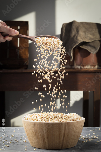 Fotografia  Pearl barley in a wooden spoon pours grains in wooden bowl