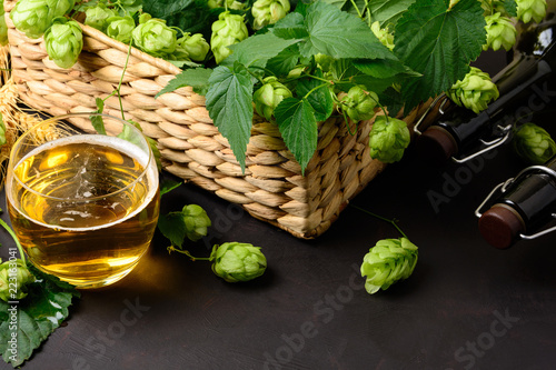 Poster Bier / Cider Glass of beer with green hops and wheat ears on dark wooden table. Still life