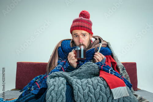 Photo  Bearded sick man with flue sitting on sofa at home or studio with cup of tea covered with knitted warm clothes