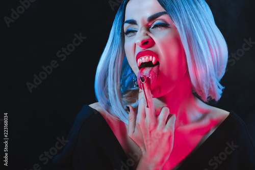 Obraz na plátně vampire woman licking her middle finger with blood isolated on black