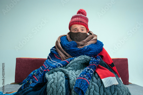 Fotografía  Bearded sick man with flue sitting on sofa at home or studio covered with knitted warm clothes