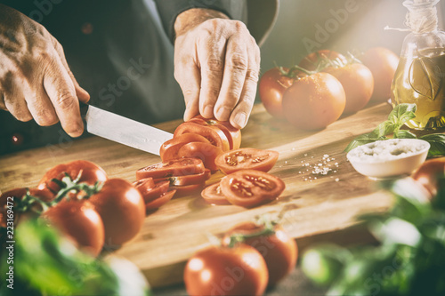 Chef slicing tomatoes in a ray of sunlight