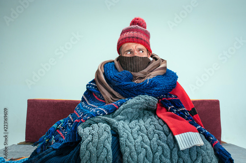 Cuadros en Lienzo Bearded sick man with flue sitting on sofa at home or studio covered with knitted warm clothes