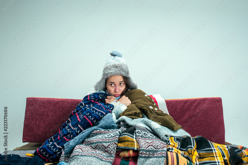 Fototapety, obrazy: The young sick woman with flue sitting on sofa at home or studio covered with knitted warm clothes. Illness, influenza, pain concept. Relaxation at Home. Healthcare Concepts.