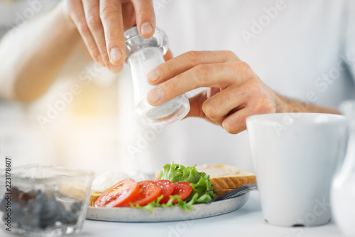 Fototapeta food, eating and people concept - close up of male hands seasoning breakfast by salt mill obraz