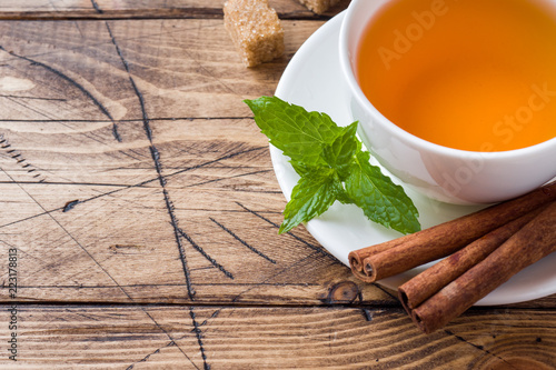 Cup of hot tea with mint and brown sugar on a wooden table Copy sapce