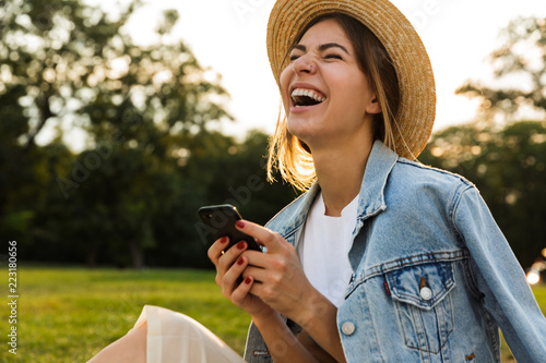 фотографія  Laughing young girl in summer hat sitting outdoors
