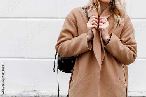 Fotografiet  Beautiful young stylish blonde woman wearing beige coat and black backpack posing near white street wall